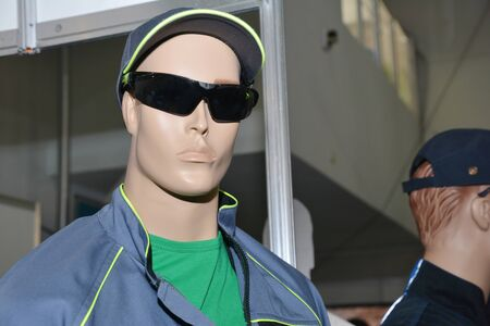 A male mannequin wearing water resistant overalls, coveralls, uniform, safety workware, T-shirt, protective glasses and ball cap, baseball cap. Stock Photo