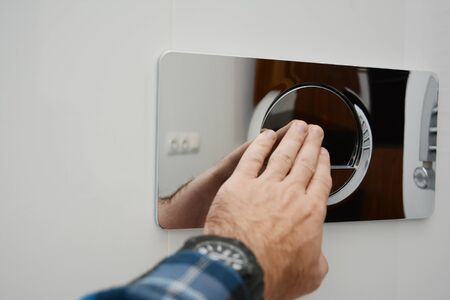 A man is pressing a wall-mounted polished chrome single flush plate to flush the toilet. Imagens