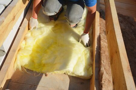 A building contractor is applying mineral wool thermal insulation under the sheathing, between roof trusses in roofing construction.