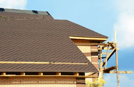 A close-up on unfinished roofing construction, covered with dimensional asphalt roof shingles, and brick walls of the house with scaffoldings against blue sky.