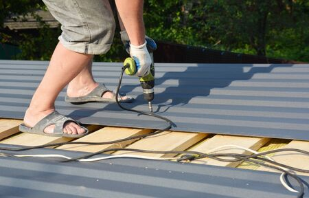 A building contractor is installing box profile sheeting, paint coated metal roofing sheets on the rooftop of the house using electric screwdriver.