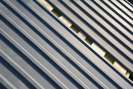 A close-up on stainless steel paint coated gray metal corrugated galvanized roofing sheets, panels installed on the roof of the house construction.