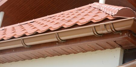 A close-up on red metal tile rooftop with wood soffit, house eaves, rafters and installed rain gutter.