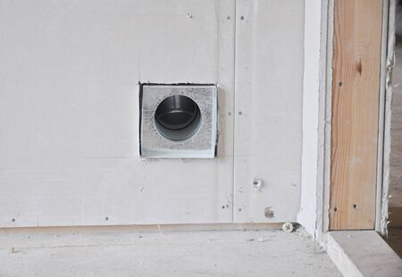 Installing an internally fitted round air vent and duct in a drywall near the door entrance during house renovation.