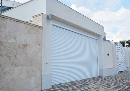 A close-up on a modern garage for cars with white garage door and lightning lamps. Stockfoto