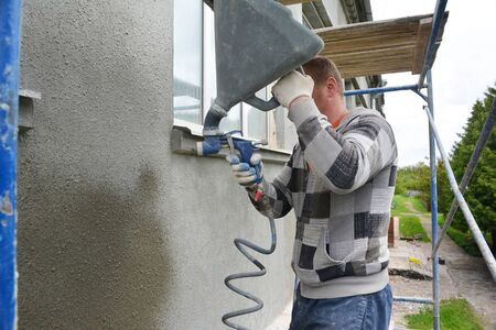 A building contractor on scaffolding is applying stucco, rendering, plastering, coating the exterior wall around the window using a plaster mortar sprayer hopper gun during house renovation.