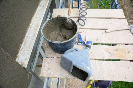 A close-up on a bucket with mortar, pvc plaster sprayer machine, stucco concrete sprayer gun, working tools of a building contractor while rendering the exterior wall of the building.