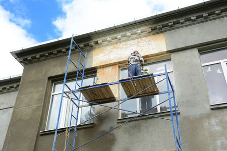 A building contractor high on scaffolding near the roof is plastering, lime rendering, coating the facade of an administrative building with large windows. Archivio Fotografico