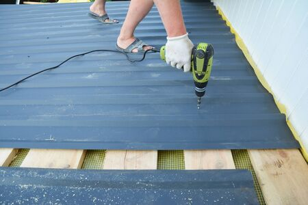 A building constructor is installing lightweight metal roofing sheet using an electric screw driver on the roof covered with yellow damp proof membrane, vapor barrier roof insulation and wood boards.