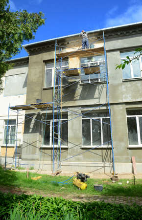 Installing high scaffolding to render, plaster, stucco, coat exterior wall of the building with large windows.