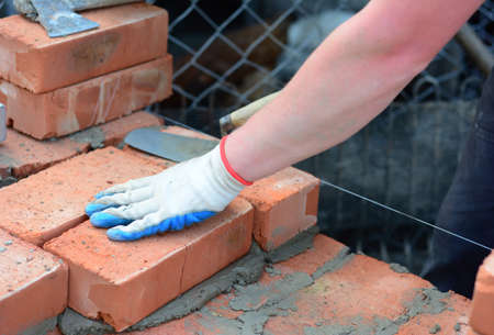 A building contractor in protective gloves is laying bricks using a mason's line, spade trowel and mortar to construct a wall of a new house.
