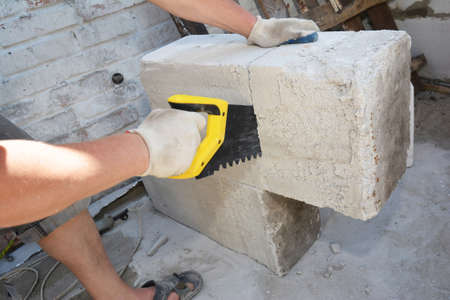 A building contractor is cutting autoclaved aerated concrete block, gas concrete using a hand saw on a construction site. Imagens