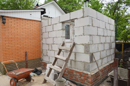 Building home addition from aerated autoclaved concrete blocks to a brick house. Stockfoto