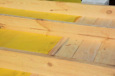 Installing vapor barrier or damp barrier membrane under wood braces, boards while constructing the roof of the house. Stockfoto
