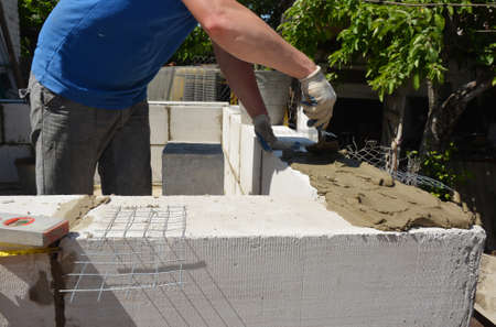 A mason or building contractor is laying a brick wall from concrete autoclaved aerated blocks, applying mortar using a trowel and reinforcing wire mesh to build home addition. Stockfoto