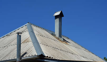 A close-up on asbestos tiled hip roof with two chimney stacks against blue sky.