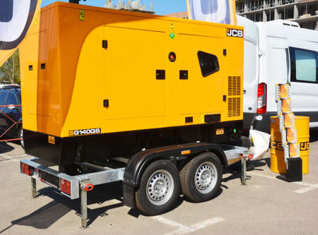 KYIV, UKRAINE - JUNE, 22, 2020: A yellow four wheels soundproof mobile power unit diesel generator mounted to a travel camping trailer. Mobile generator.