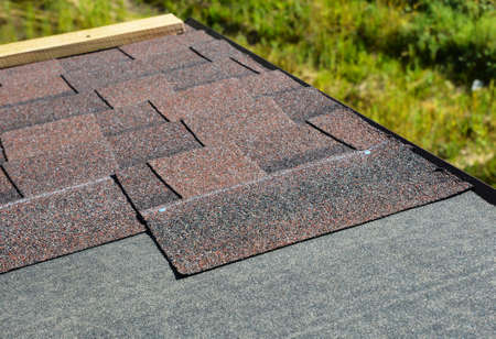 Laying asphalt shingles on house rooftop. Roofing construction concept