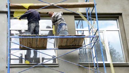 Two building contractors on scaffoldings are plastering, applying stucco finish, rendering, coating the facade wall of a house.