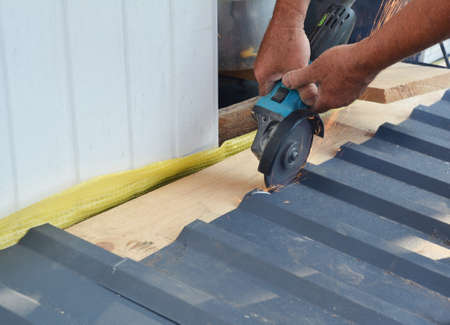 A building contractor is cutting lightweight metal, steel, corrugated, paint coated roofing sheet with an electric angle grinder laying profile sheet on the ground across padded support.