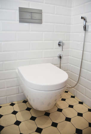 A retro renovated toilet room with white tiled walls, yellow and black vintage floor tiles, a wall mounted ceramic toilet bowl, and a hand held bidet shower.