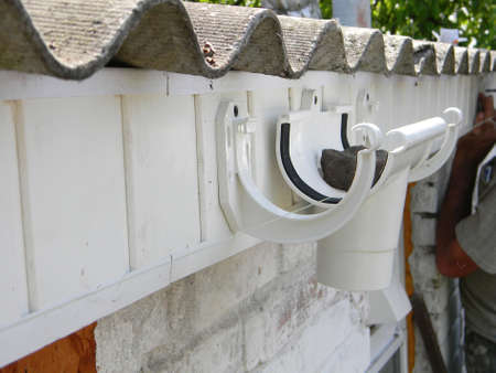 A close up on a plastic running outlet and fascia brackets fixed to the fascia board during rain gutter system roof installation. Imagens
