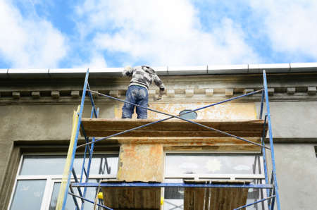 A building contractor on scaffoldings is plastering, applying stucco and renovating painting the facade of a building.