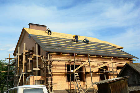 Roofing contractors are installing underlayment, water-resistant, waterproof protection barrier on the roof deck of a large brick house construction with scaffoldings before asphalt shingles covering. Archivio Fotografico