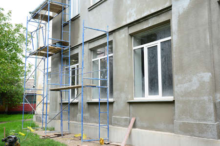 Renovating the facade of a building by applying stucco finish, plastering and finishing the exterior walls using scaffold or staging. Archivio Fotografico