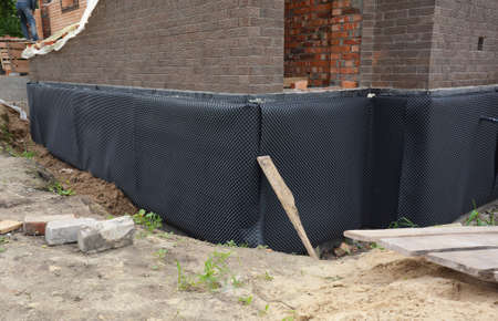 Example of bad and ineffective applying of non continuous and not total exterior waterproofing membrane to the outside of the foundation wall to prevent water infiltration.