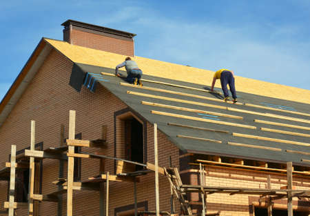 Roofing contractors are installing underlayment, waterproofing membrane on a roof deck, plywood sheathing of a large brick house under construction with scaffolding.