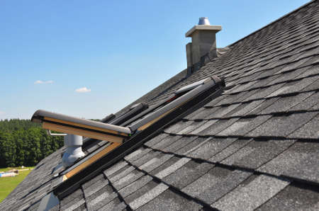 A gray roof covered with dimensional architectural asphalt shingles with an attic skylight, ventilation pipe, air duct and chimney. A close-up on an open attic skylight.