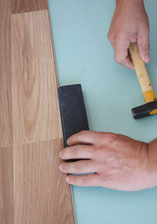 A handyman is installing a wood laminate flooring on the underlayment using a hummer along with a tapping block to snug up the joints of a floating laminate flooring planks. Stock Photo