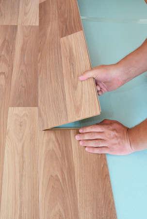 Wood laminate flooring installation: a handyman is laying the laminate flooring plank on the underlayment till it snaps.