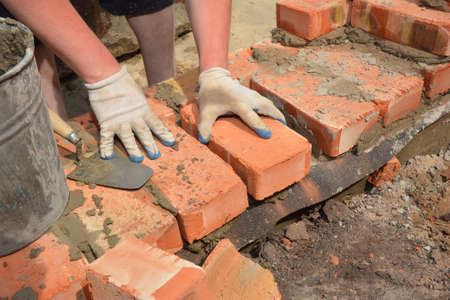 A bricklayer is laying the first row of bricks on a concrete foundation or footing above a damp proof course, a layer of impermeable bitumen barrier to prevent ground water upward migration.