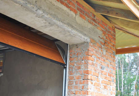 Panel garage door installation for a car garage inside of the house under construction.