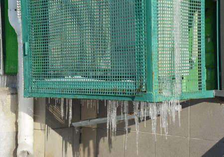 An outside air conditioner unit frozen, freezing up with a lot of icicles in winter, HVAC unit covered with ice in winter. 免版税图像