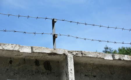 High security fencing: A close-up of a concrete security fence with barbed wire, steel razor wire to protect the property from intruders.