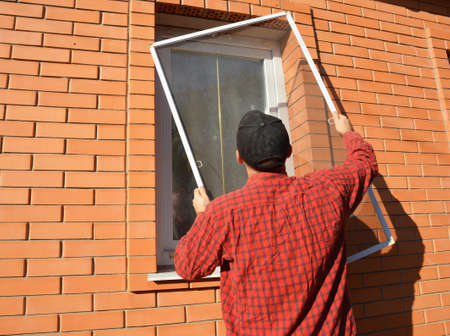 A man is installing a mosquito screen, net, panel insect screen on the window outdoors to protect his house from flies, mosquitos and bugs. 免版税图像