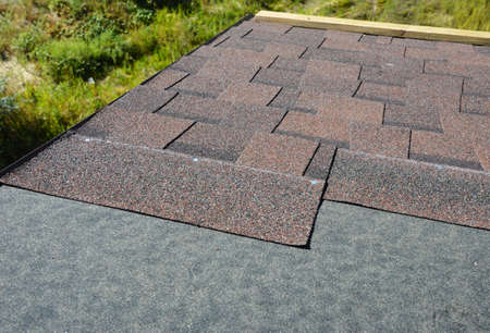 Installing brown dimensional asphalt roof shingles on the underlayment, water-resistant, waterproof protection barrier material on the rooftop of the house construction during house repairing. Stock Photo