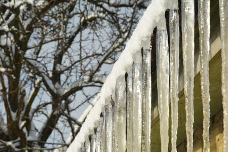 Large icicles are hanging along the edge a house roof as a sign of roof problems. Ice dams on the roof in winter.