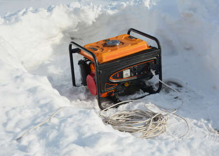 Usage of gasoline portable outdoor generator, home power generator to backup the house during blackouts, outages as a result of a winter storm.