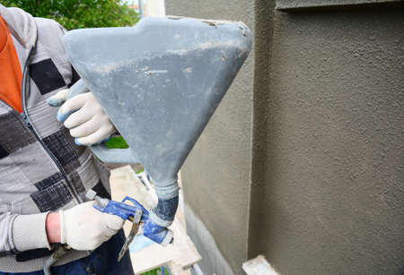 A building contractor is renovating, rendering exterior walls of the house, applying stucco, spaying texture using a texture air spray gun.