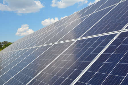 A close-up on a solar panel with numerous solar modules and photovoltaic cells against blue sky with white clouds as a source of alternative, renewable green energy.