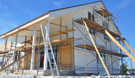 Modern house repair and renovation. Plastering, applying stucco and painting the facade walls using scaffoldings during house renovation. Archivio Fotografico