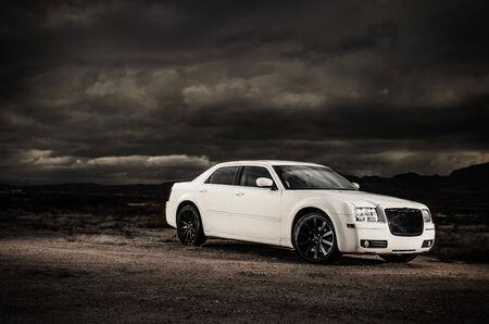 white 4 door sedan in the desert with dark storm in the background Stok Fotoğraf