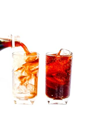 Cola being poured into a glass with ice cubes in, isolated on a white background   photo