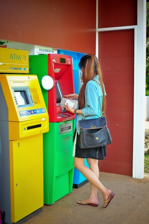 automatic teller machine: woman taking off money from the outdoor bank terminal Editorial