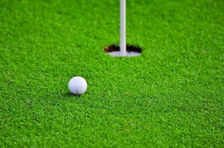 A white golf ball near the hole photo