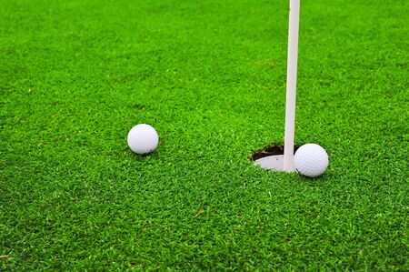 Two golf balls on golf course putting green photo